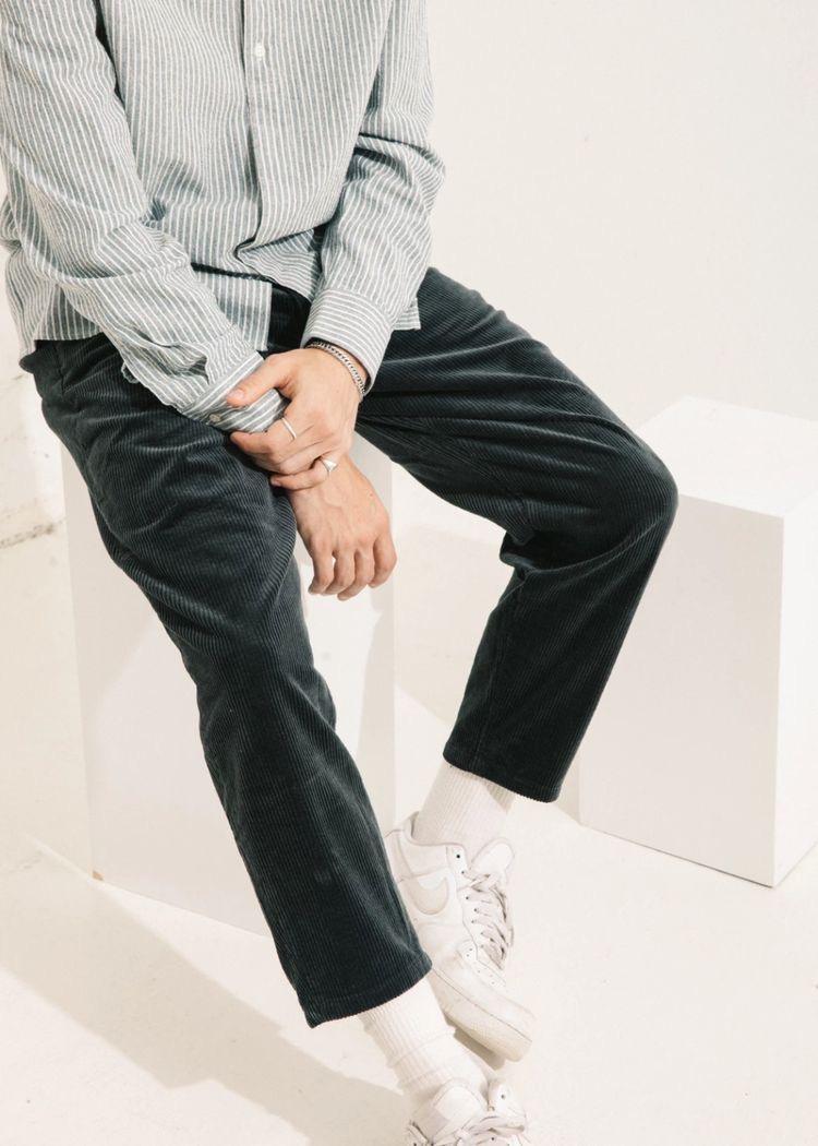 Темные мужские вельветовые брюки.
